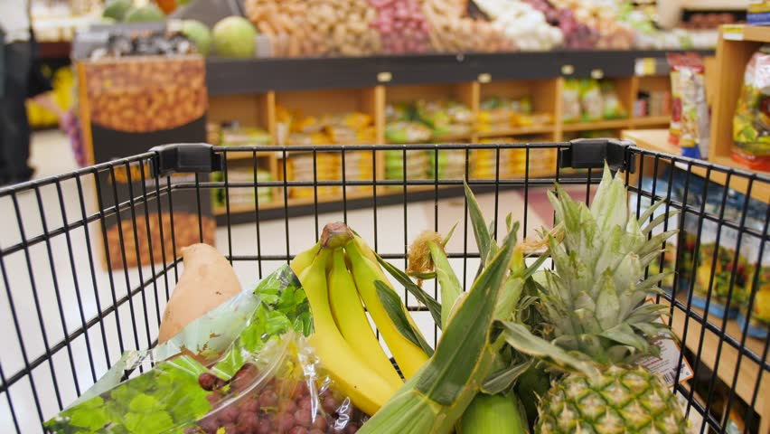 Clip of a half-full shopping cart moving through a supermarket's produce aisle. You can clearly see fruits like pineapple, bananas, and grapes inside the cart. Shot in real time.