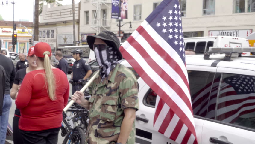 LOS ANGELES - MARCH 26, 2017: Militant White Nationalist Waving Flag Pro Trump Event Hollywood Blvd 4K LA California. The wave of white nationalism sweeping the country can be seen at Trump rallies.