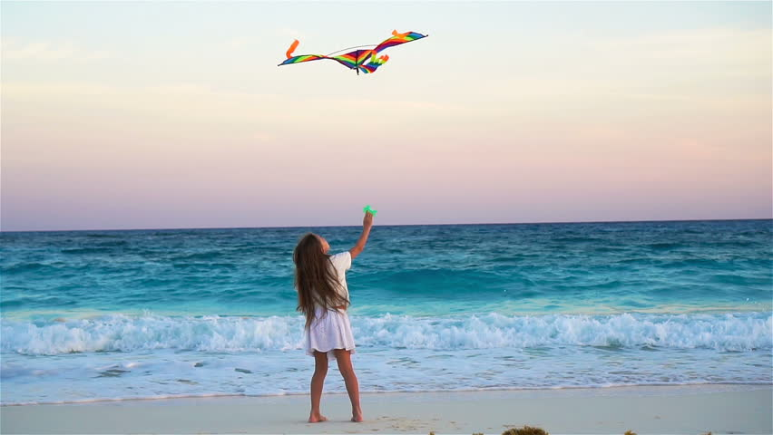 Little girl with flying kite on tropical beach. Kid play on ocean shore. Child with beach toys in slow motion | Shutterstock HD Video #27334078