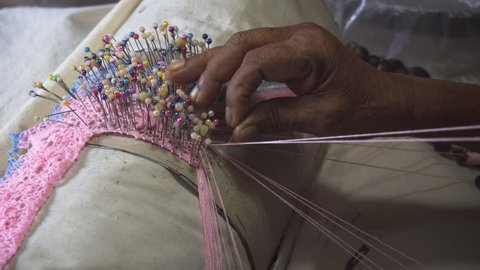 Local woman weaves fine blue and pink yarn into delicate lace. using dozens of pins with colorful heads in Sri Lanka. UltraHD 4k footage