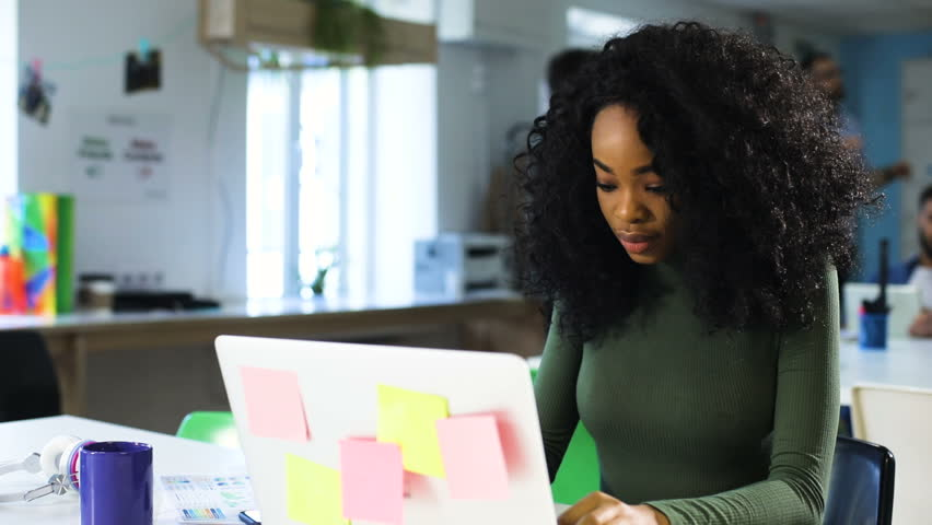 Young pretty African American woman with curly hair using a laptop in the office, feeling happy | Shutterstock HD Video #27337825