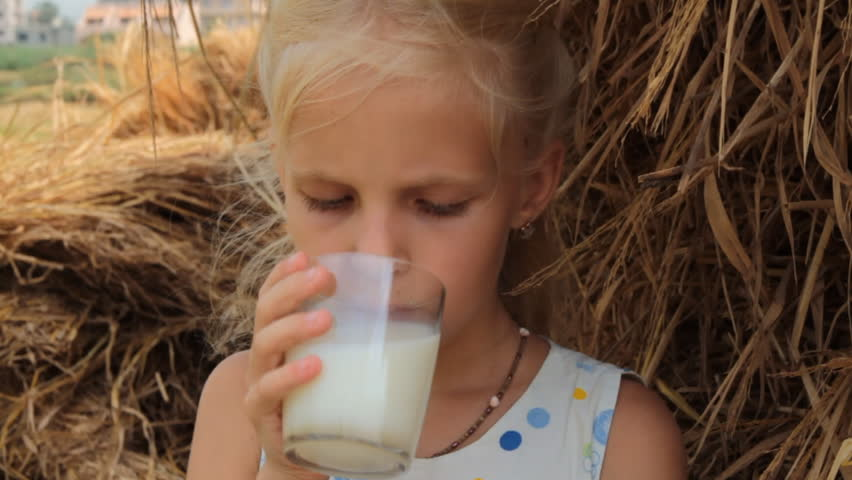 Girl drinks cow's milk from a glass against the backdrop of a haystack on a farm. The child drinks fresh milk in the summer in the village.