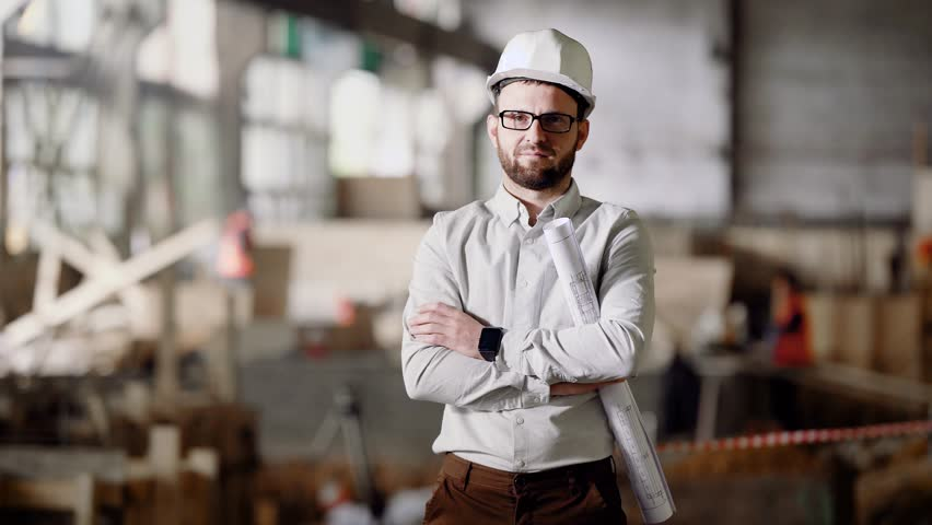 An adult architect in a helmet stands at the current construction site, in his hands a project for the modernization of an abandoned factory in the city | Shutterstock HD Video #27385300