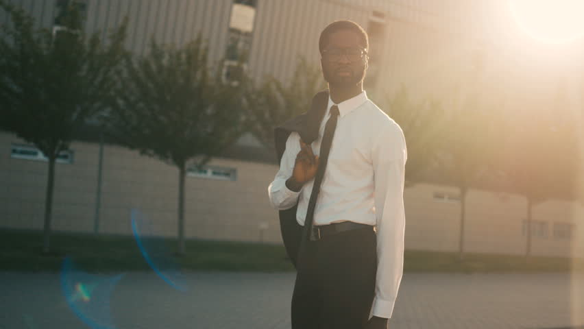 Attractive confident african american businessman walking near office center holding jacket over his shoulder. Man going home after work. Sun rays. Close up | Shutterstock HD Video #27395731