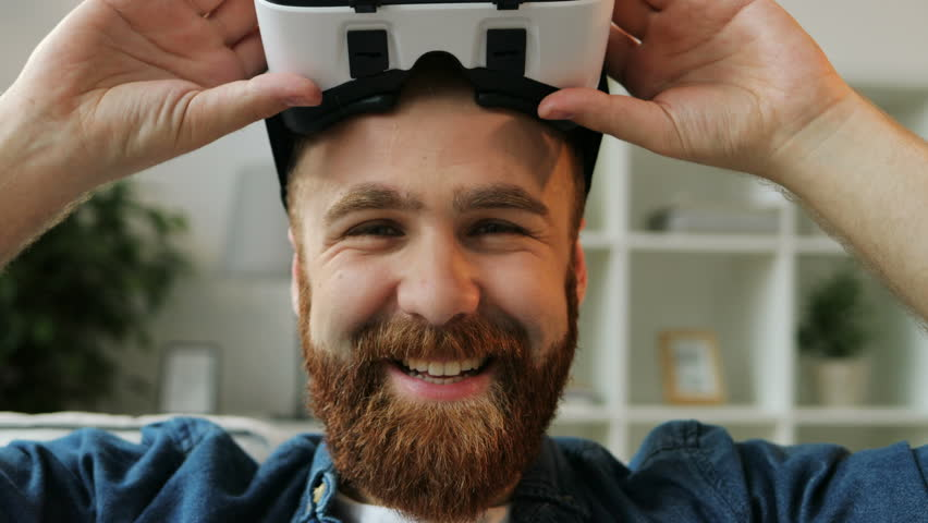 Young hipster man using his VR headset for watching the 360 video while sitting on sofa at home in the living room. Close up.