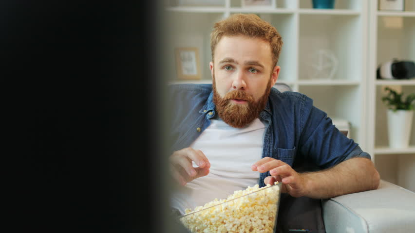 Emotional man with beard watching stressful football match, eating popcorn while sitting in the living room. #27407269