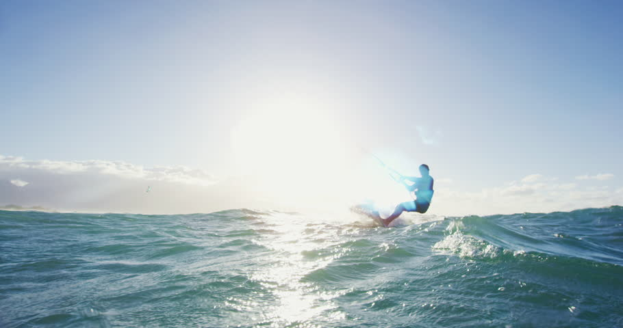 Young man kite surfing in blue ocean at sunset. Having fun outside in nature. Extreme sports summer. Shot on RED   Shutterstock HD Video #27427804