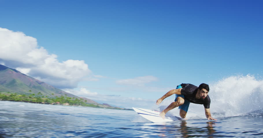 Young man surfing blue ocean wave in slow motion. Close up water shot POV. Happiness in nature. Shot on RED