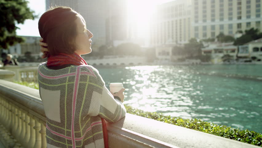 Young beautiful woman is standing in front of fountain and drinking tea | Shutterstock HD Video #27438100
