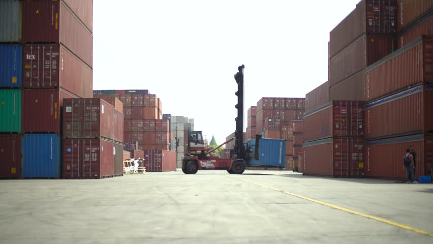 Shipping container loader truck transporting box. Shipyard piled high with containers being moved by machinery. Industrial loading yard with loading vehicle.