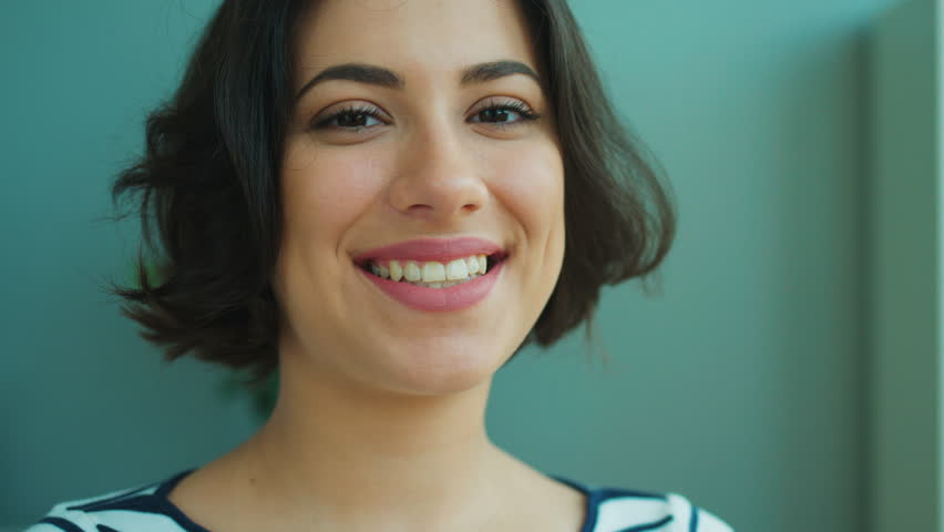 Close up woman portrait. Beautiful young woman turning head to camera and smiling. Indoors | Shutterstock HD Video #27449605