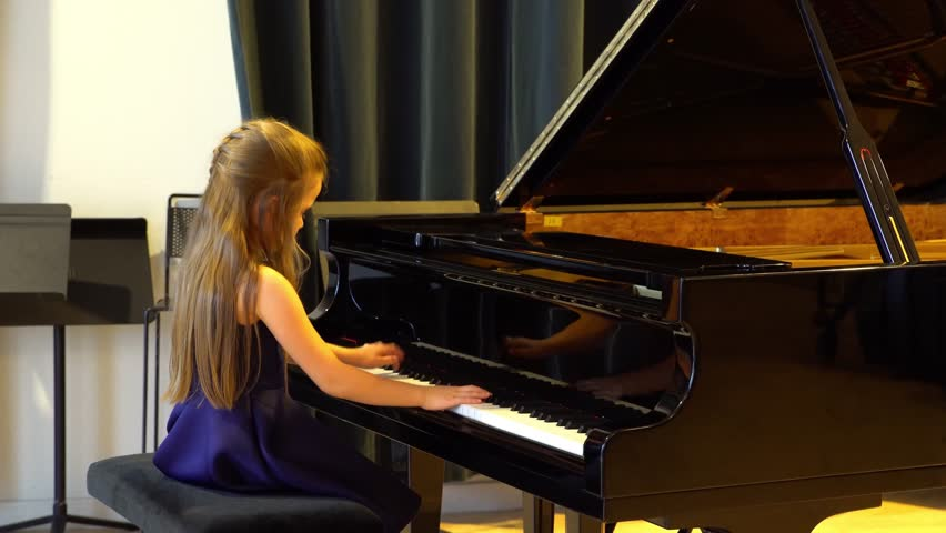 Cute preschooler girl playing J.S.Bach on grand piano, concert of little talents