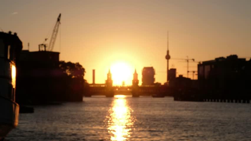Berlin, Germany - june 02, 2017: Train crossing Oberbaumbruecke (Oberbaum Bridge) /  river Spree with  Tv Tower ,  and sunset sky background in Berlin.