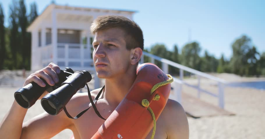 A beach lifeguard with a bare torso looks through binoculars watching suspicious personalities. Royalty-Free Stock Footage #27473770
