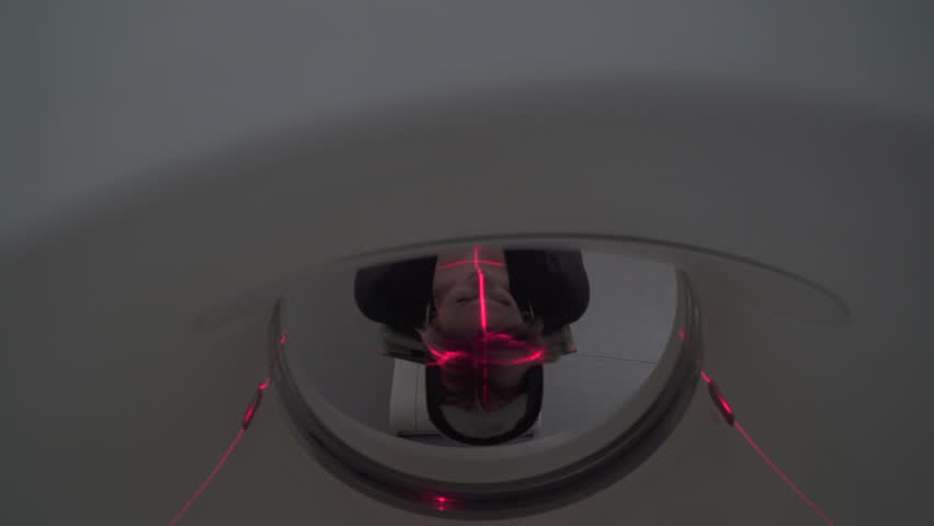 Woman lying on the CT or MRI scanner during machine imaging her body, lights up infrared rays and female patient passes through the circle, crane shot from down to up, room interior, active scene.