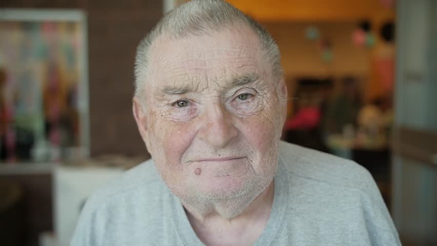 Slow-motion clip of an old, Caucasian man raising his eyebrows and flashing the camera a faint smile. He has gray hair and a mole/wart under his lip.  | Shutterstock HD Video #27494413