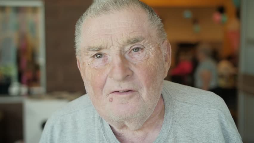 In this video, an old Caucasian man with a mole/wart below his lips looks at the camera. Camera goes in and out of focus. Shot in slow motion. | Shutterstock HD Video #27495034