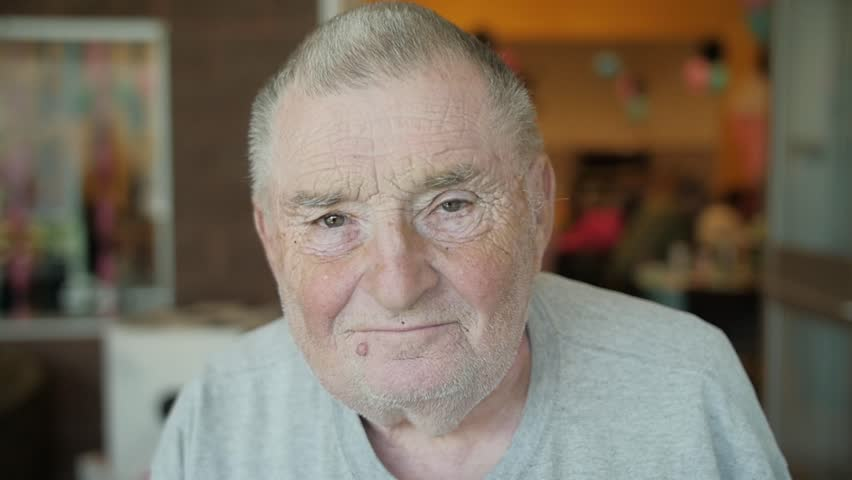 "In this video, an old Caucasian man in a gray shirt and with a mole/wart below his lips smiles at the camera awkwardly and mouths ""Okay."" 