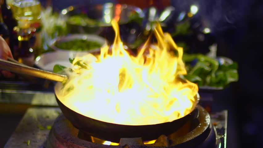 Street-side wok fire in Shanghai slow motion. Slowmo cook fires up hot oil with vegetables outside on the road at night in downtown Shouning rd food street in China. | Shutterstock HD Video #27505327