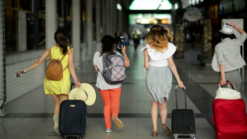 Four Female Friends in Bright Summer Clothing are Late for Their Plane. Beautiful Girls are Running inside the Airport with Documents, Tickets, and Large Suitcases in Hands.