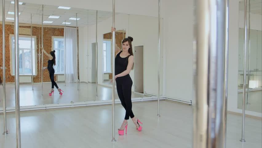 Flexible gymnast shows her skill on a pylon in a studio #27527986