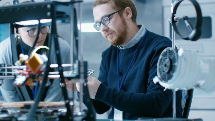 Young Talented Male and Female Engineers In a Modern Laboratory Construct Prototype with the Help of 3D Printer. Shot on RED EPIC-W 8K Helium Cinema Camera. Shot on RED EPIC-W 8K Helium Cinema Camera.
