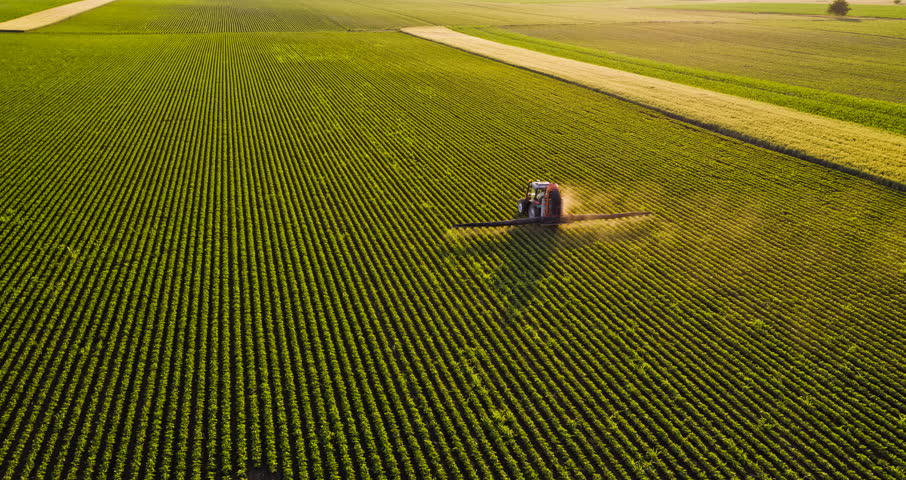 Aerial drone shot of a farmer spraying soybean fields #27569626