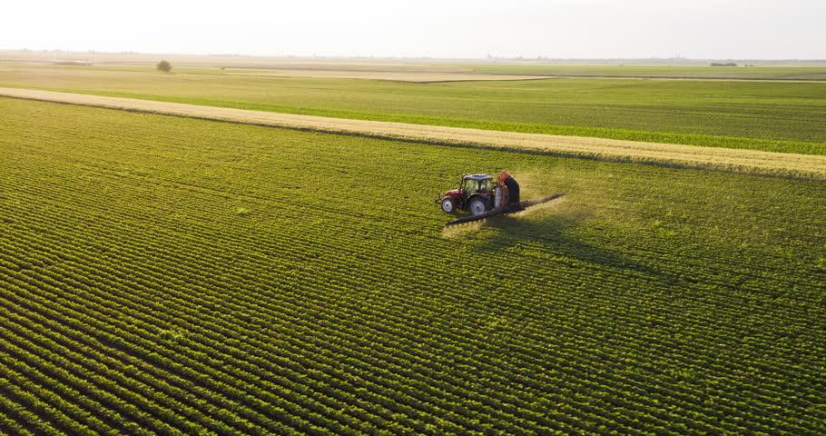 Aerial drone shot of a farmer spraying soybean fields Royalty-Free Stock Footage #27569629