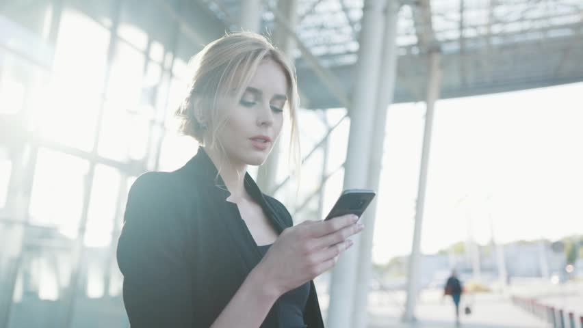 A beautiful blonde woman in a formal black outfit stands by the airport entrance, uses her cell phone, gets the text message, being surprised, smiles happily and looks around.