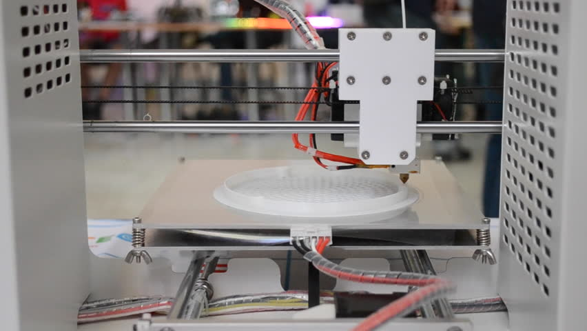 3d printer printing white round model backside. Many people in the background blurred plan close-up.