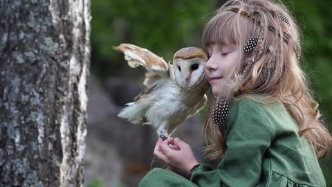 Little girl with an owl in a fairy forest