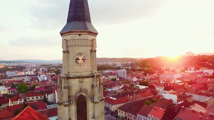 Aerial view of Cluj, in the heart of Transylvania, Romania. Pan shot of the church medieval tower in the city center, at sunset.