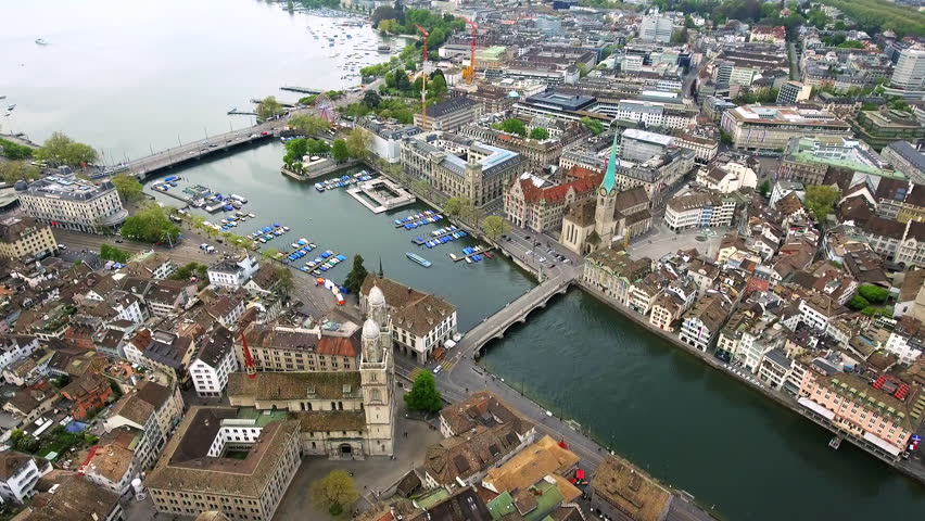 Helicopter View Aerial Video of Zurich Landmarks in City Center Town Hall Fraumünster Church, Iconic Romanesque cathedral : Grossmünster, Historic Gothic Church with a Large Clock Tower : St. Peter 4K