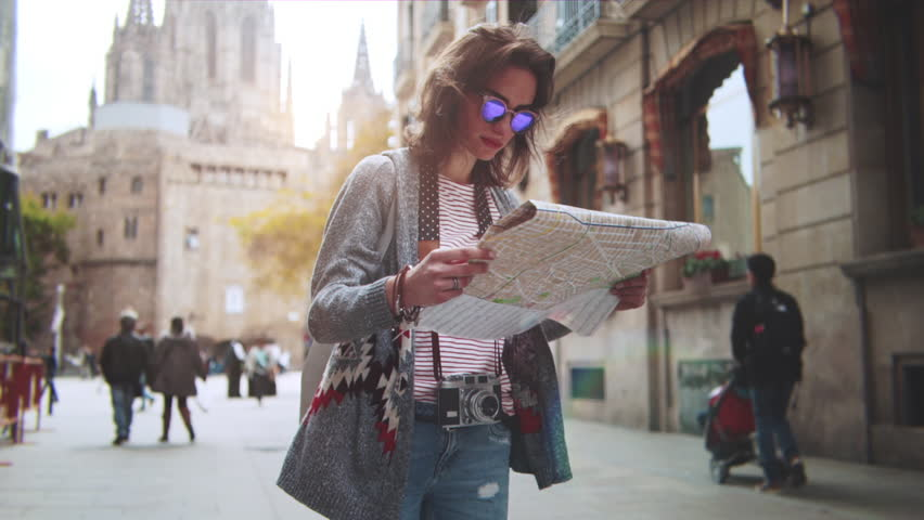 Back view of young hipster girl walking through European street and exploring Barcelona city with map, travel vacation adventure concept, slow motion