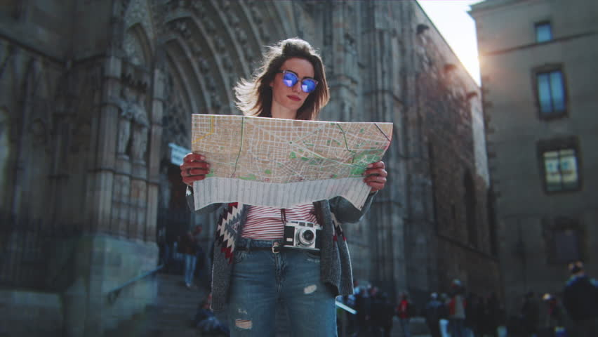 Attractive young woman traveling in Europe and exploring beautiful sightseeing in Barcelona, sunshine lens flare, slow motion, hipster girl wearing glasses and holding tourist map, enjoying holiday  Royalty-Free Stock Footage #27590053