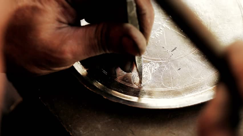 Traditional tinsmith work. Copper smith makes embossing artifacts from copper. Designing utensils, the age old art of crafting wares. Copper engraving. Souvenirs. Shooting close-up Copper smith work.