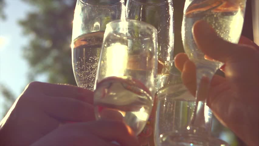 Group of people toasting and drinking champagne on the restaurant terrace over sunset. Celebrating. Glasses with Sparkling Champagne over nature Background. Resort. 4K UHD video 3840X2160