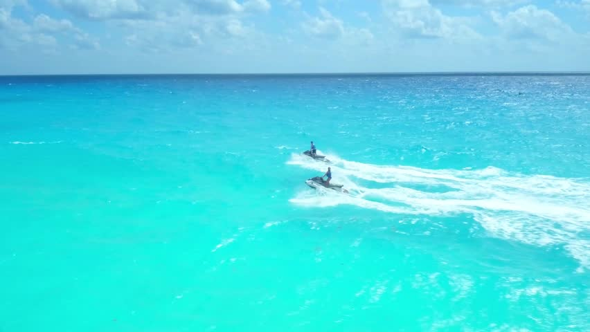 Man and Women on Jetskis in Blue Ocean