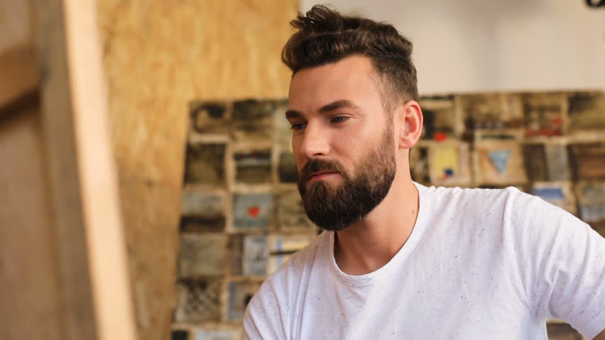 Young attractive bearded artist paints a picture in the studio | Shutterstock HD Video #27606886