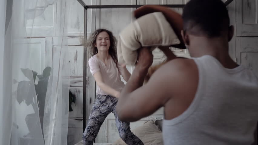 Fight by pillows of man and woman in pajamas. Loving multiethnic couple have fun, carefree morning together. Slow motion | Shutterstock HD Video #27622765