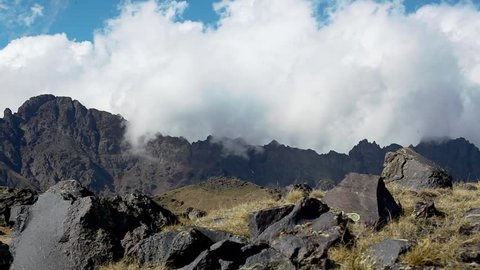 White and grey clouds make their way through the mountain range