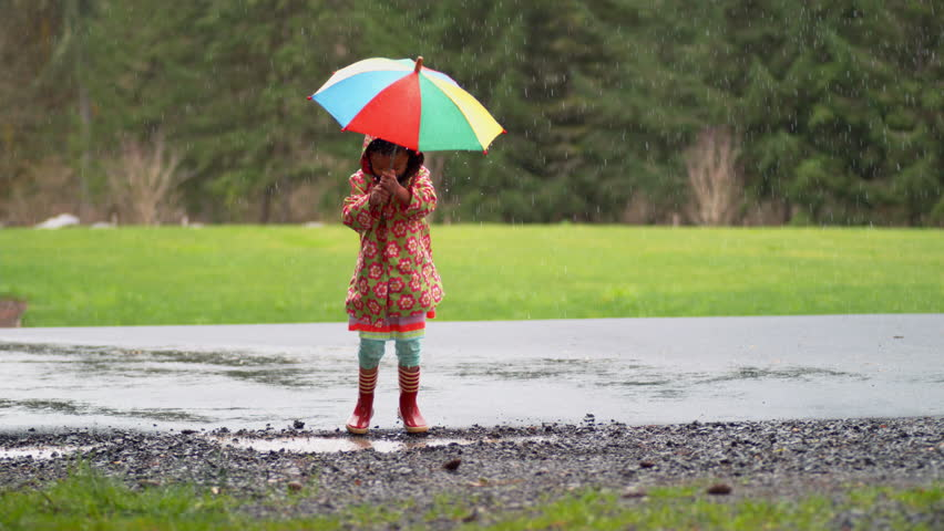 Young girl with umbrella playing in rain, slow motion, shot with Phantom Flex 4K