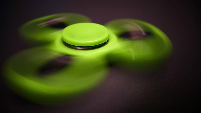 Close up and low angle footage of a green spinning fidget spinner...