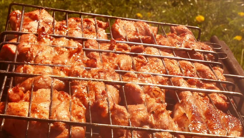 Delicious meat steak cooking on the grill. Closeup. The camera slides along the grill with chicken legs and meat steak.   Shutterstock HD Video #27632452