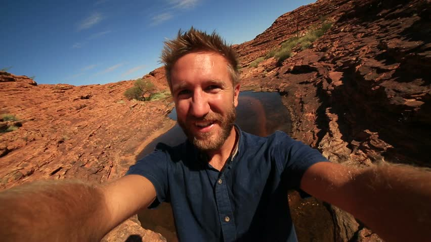 Travel man hiking takes selfie portrait Young man hiking in Australia take a selfie portrait with the landscape of kings canyon in outback, red centre of Australia.