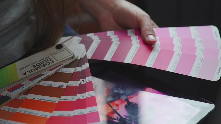 Color model Pantone, PMS (Pantone Matching System). Selection of colors for the Panton system. Creative people workplace. Close-up view of hands of young designer woman working with color palette. Royalty-Free Stock Footage #27637381