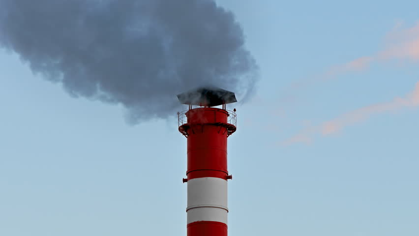 Smoke stack. Smoke comes from red-white chimney on thermoelectric plant against sky.