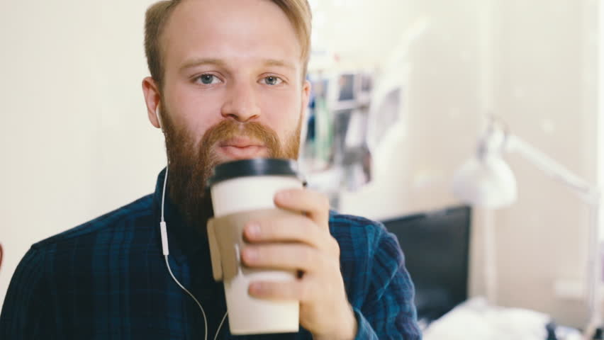 Hipster man drinking coffee at desk in creative office | Shutterstock HD Video #27661801