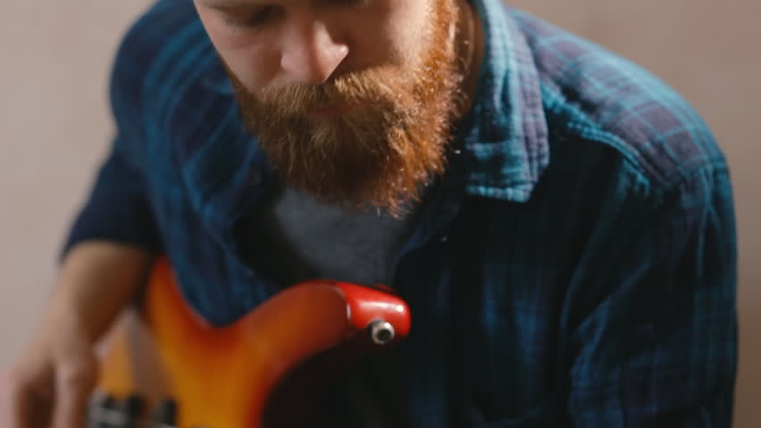 Young fashionable Bearded hipster playing guitar playing melody at bass guitar