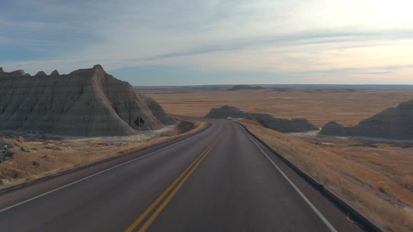 Descending down the road past big rocky sandstone mountains in Badlands National Park on autumn evening. Driving on empty road towards vast grassland, leaving picturesque sandstone formations behind